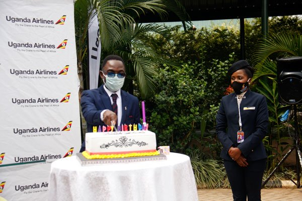 Uganda Airlines CEO, Mr Cornwell Muleya cuts a cake to celebrate the Airlines' first anniversary on August 28, 2020